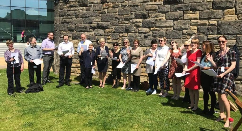 So Choir! Wellington Place Workplace Choir in Leeds singing outside on the grass and enjoying the sunshine